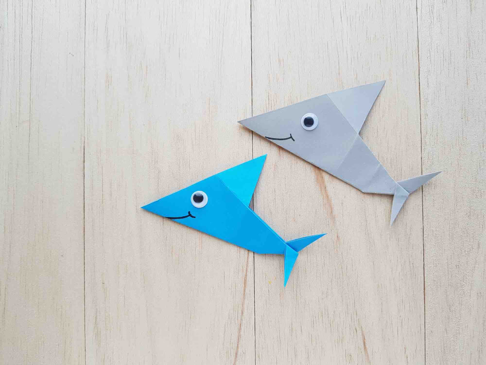 Learn how to make an origami shark by top Hawaii blog Hawaii Travel with Kids. Image of 2 origami sharks with googly eyes.