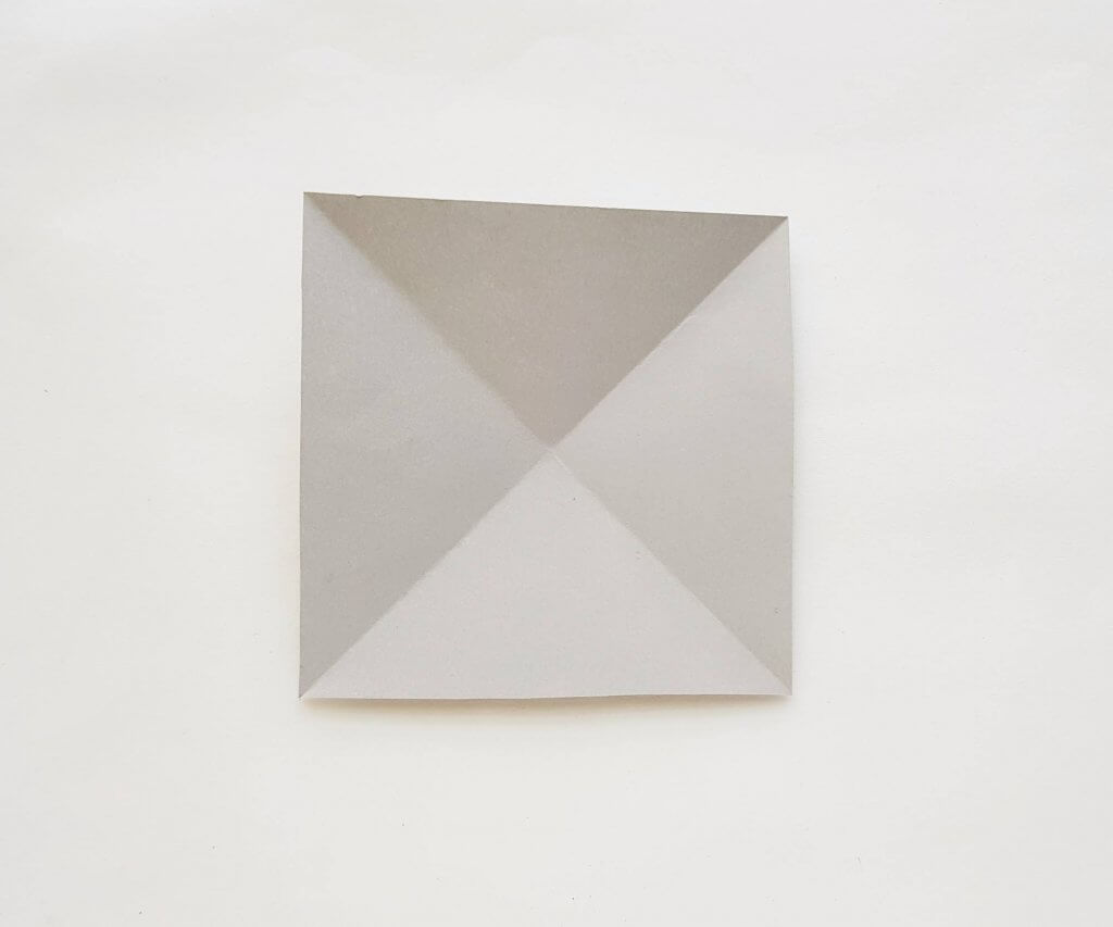 Learn how to make an origami shark craft. Image of a grey square paper folded twice.