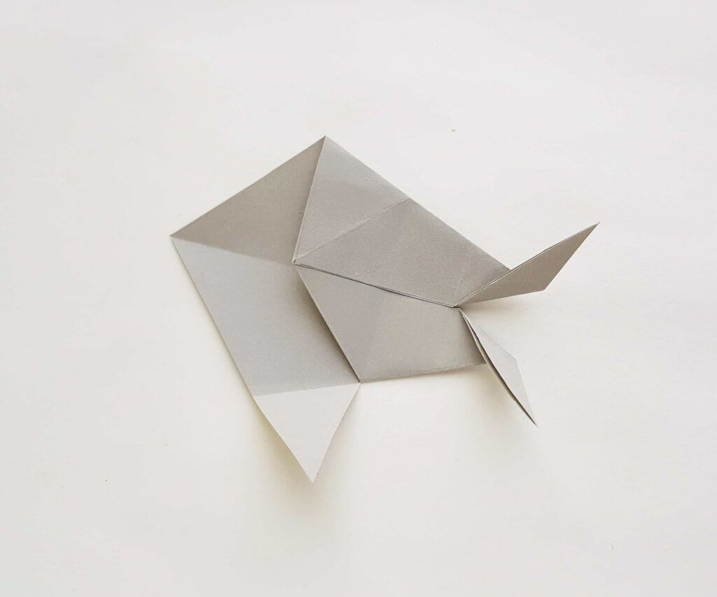 Get this step by step tutorial on how to make an origami shark. Image of a grey paper folded to look like a shark.