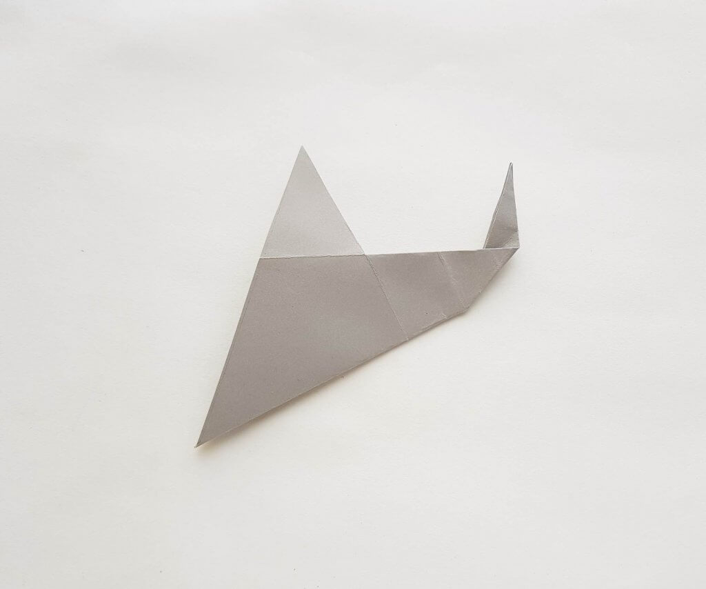 Get this easy shark craft tutorial. Image of a grey paper folded to look like a shark.