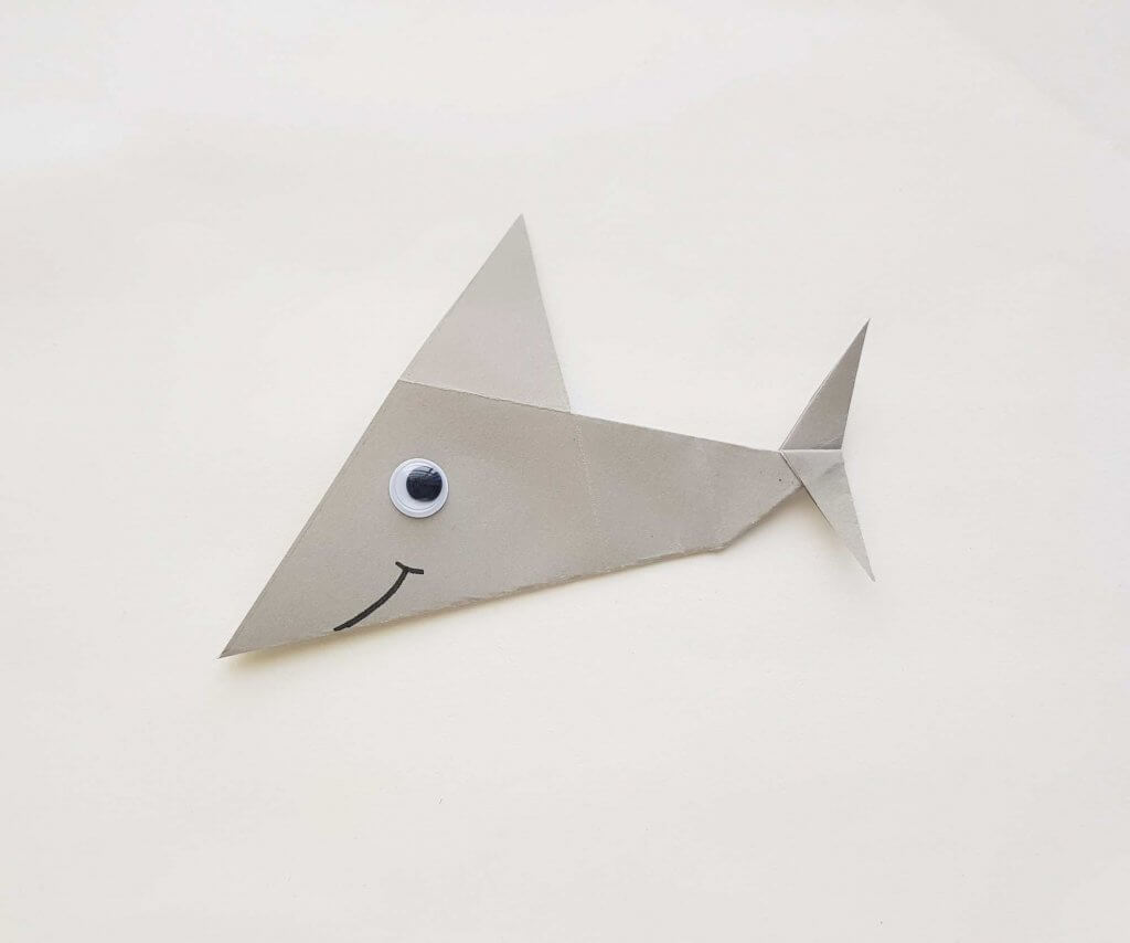 Make your own origami shark with this easy shark origami tutorial. Image of a paper shark with a googly eye and Sharpie smile.