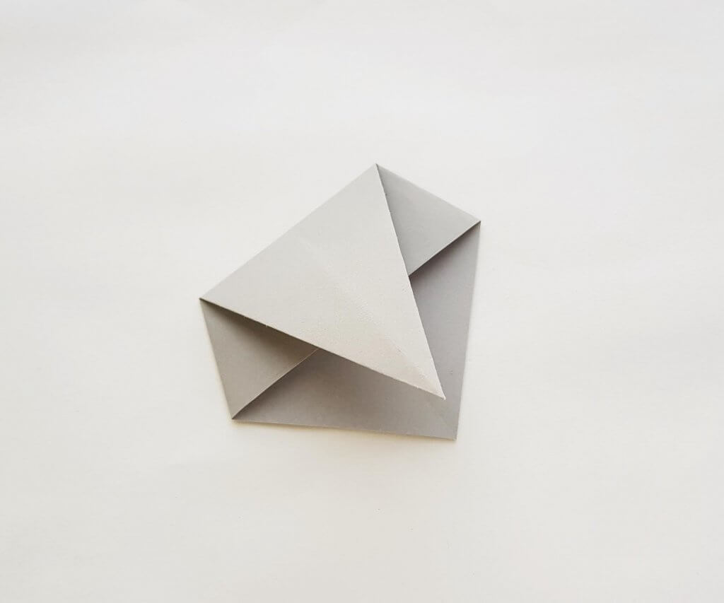 Learn how to make a origami shark out of paper. Image of a grey piece of origami paper that has been folded.