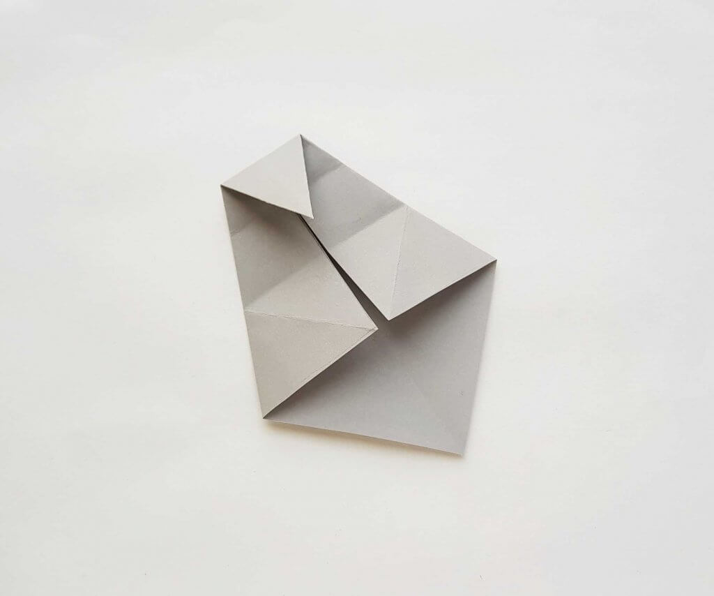 Get my easy origami shark tutorial. Image of a grey paper folded a bunch of times.
