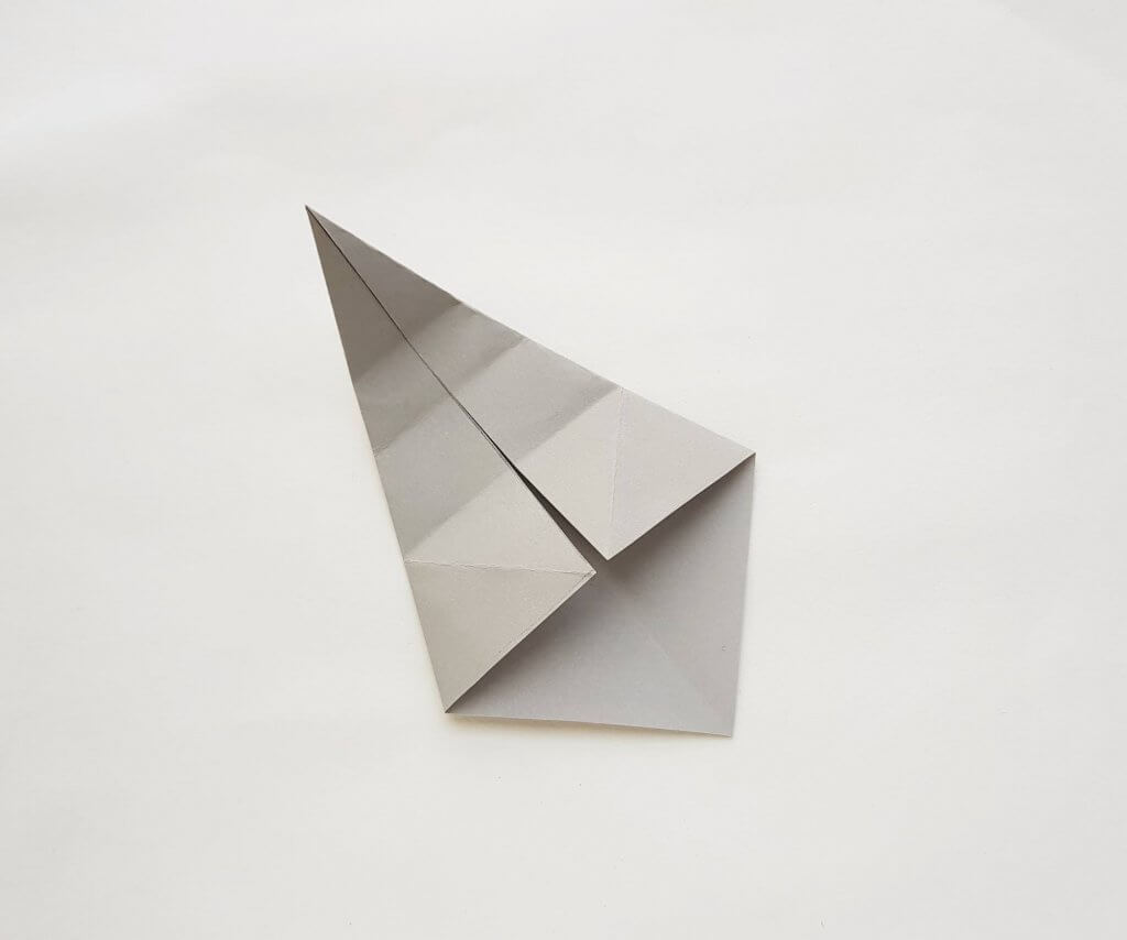 Get my origami shark instructions. Image of a piece of grey paper folded and unfolded