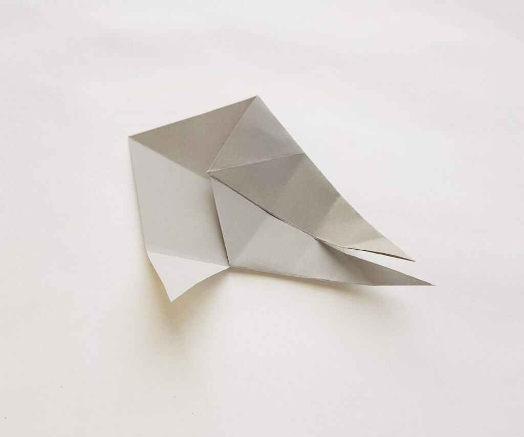 Learn how to make an origami shark out of paper. Image of a piece of grey paper that is folded to look like a shark.
