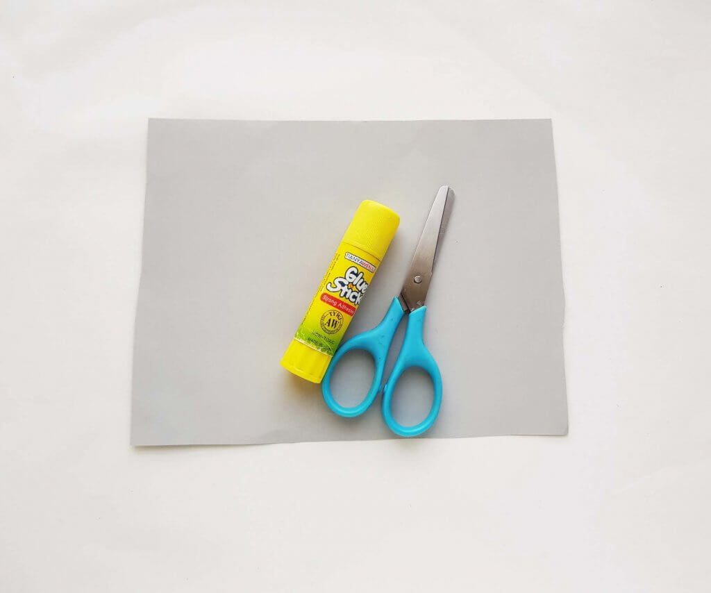 Image of materials to make an origami shark, including scissors, a glue stick, and paper.