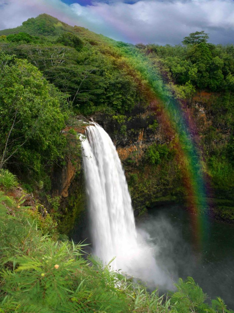Find out all the best places to see in Hawaii by top Hawaii blog Hawaii Travel with Kids. Image of Waterfall in Hawaii With a Colorful Fantastic Rainbow