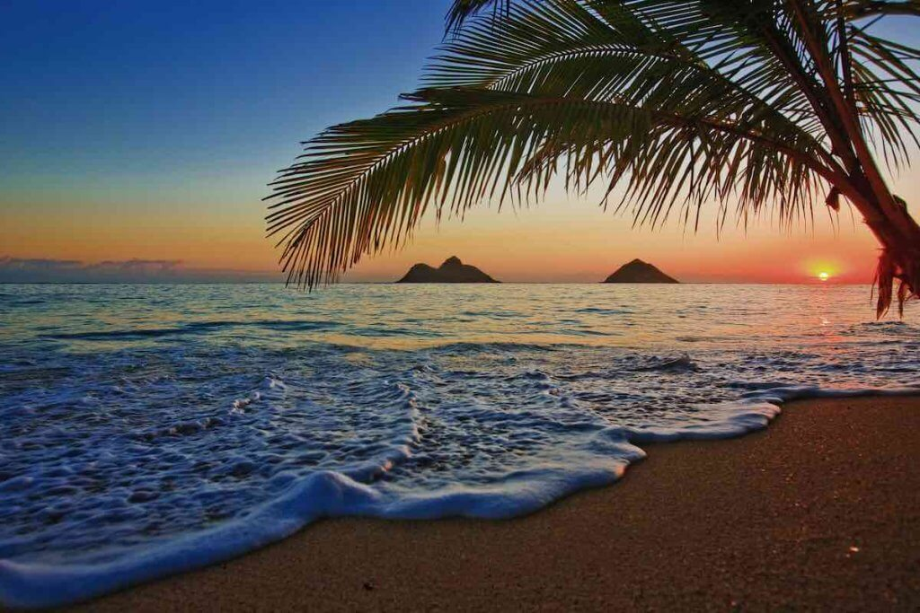 One of the best free things to do in Oahu on your first morning is to see an Oahu sunrise. Image of sunrise at Lanikai beach on Oahu.