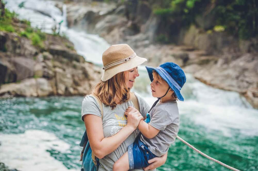 Find out 101 things to do in Maui with kids by top Hawaii blog Hawaii Travel with Kids. Image of Mother and son relaxing under a waterfall. Vacation concept.