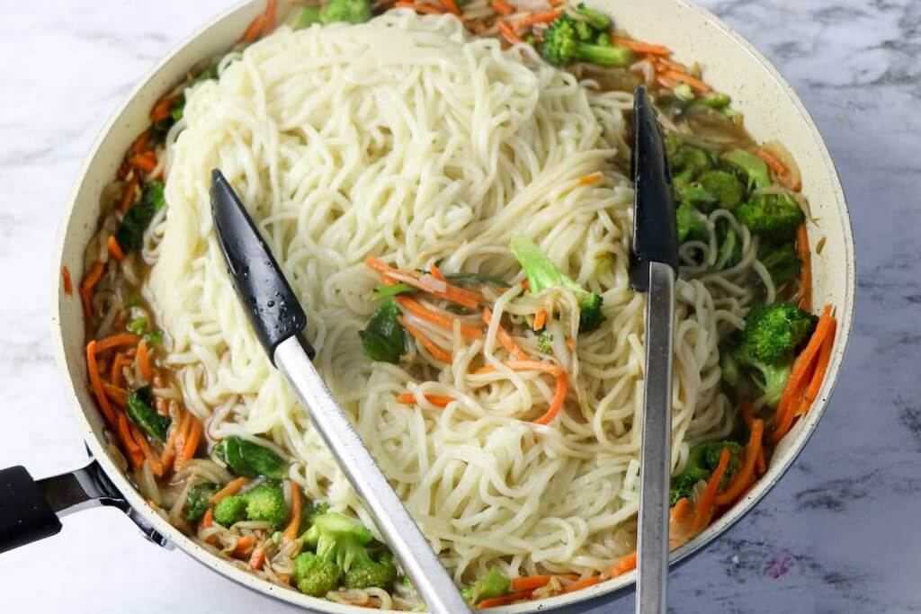 Add in the cooked lo mein noodles and toss together. Image of veggies and noodles in a skillet.