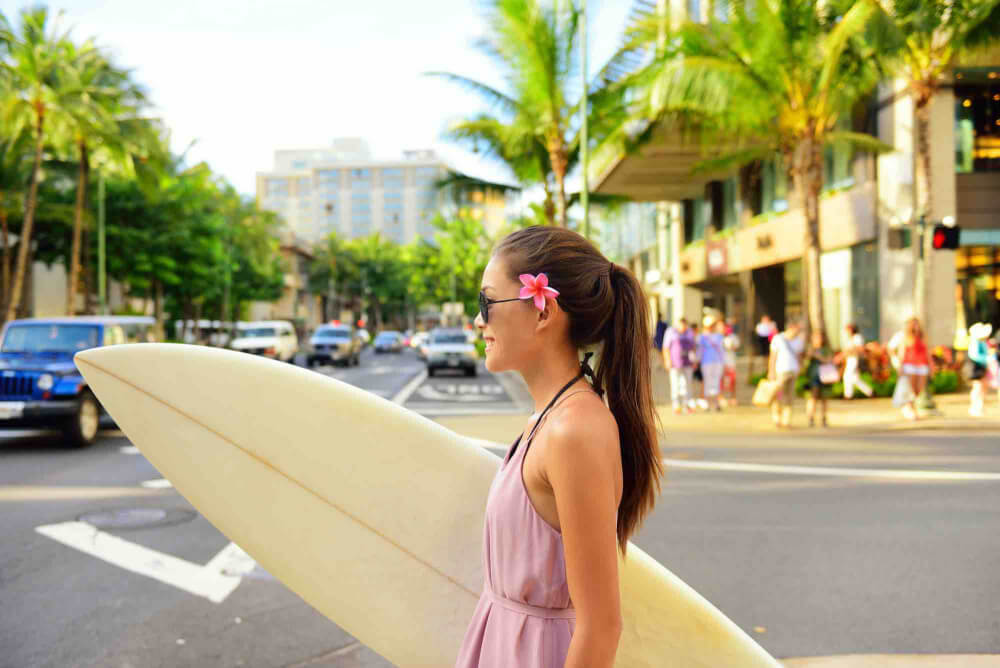 Find out the best Oahu planning tips from top Hawaii blog Hawaii Travel with Kids.Image of Surfer woman walking in city with surfboard to go surfing. Urban Hawaiian surf concept. Asian girl holding surf board crossing street to go to the beach. Waikiki, Honolulu city, Oahu, Hawaii, USA.