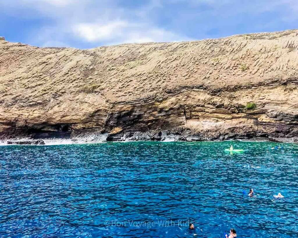 Find out the best Hawaiian island for snorkeling in this post by top Hawaii blog Hawaii Travel with Kids. Image of a bunch of people snorkeling in Hawaii off the coast of Molokini Crater Maui.
