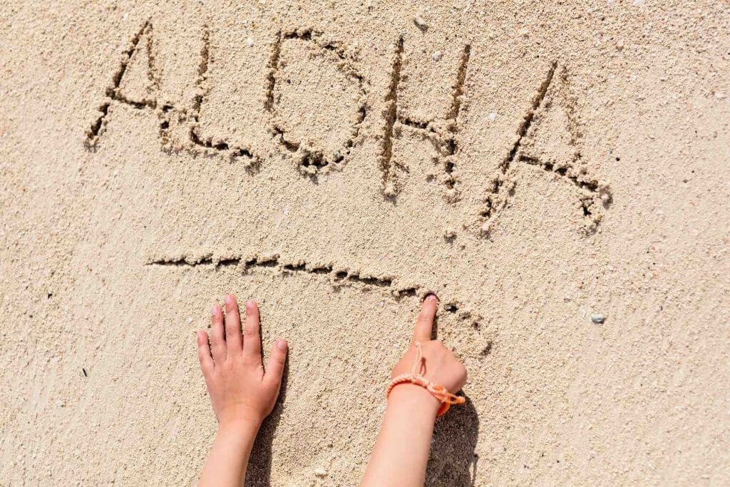 "It's helpful to learn a few words in the Hawaiian language before your trip. Image of the word ""aloha"" written in the sand."