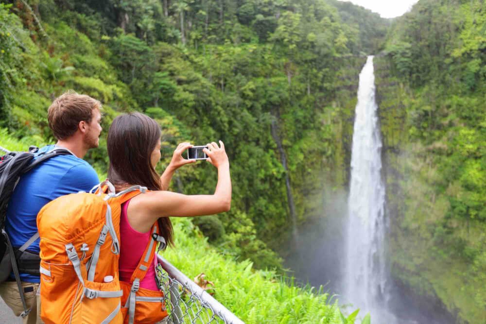 Find out my top Hawaii Big Island Vacation tips from top Hawaii blog Hawaii Travel with Kids.Image of a couple of tourists on Hawaii by waterfall.