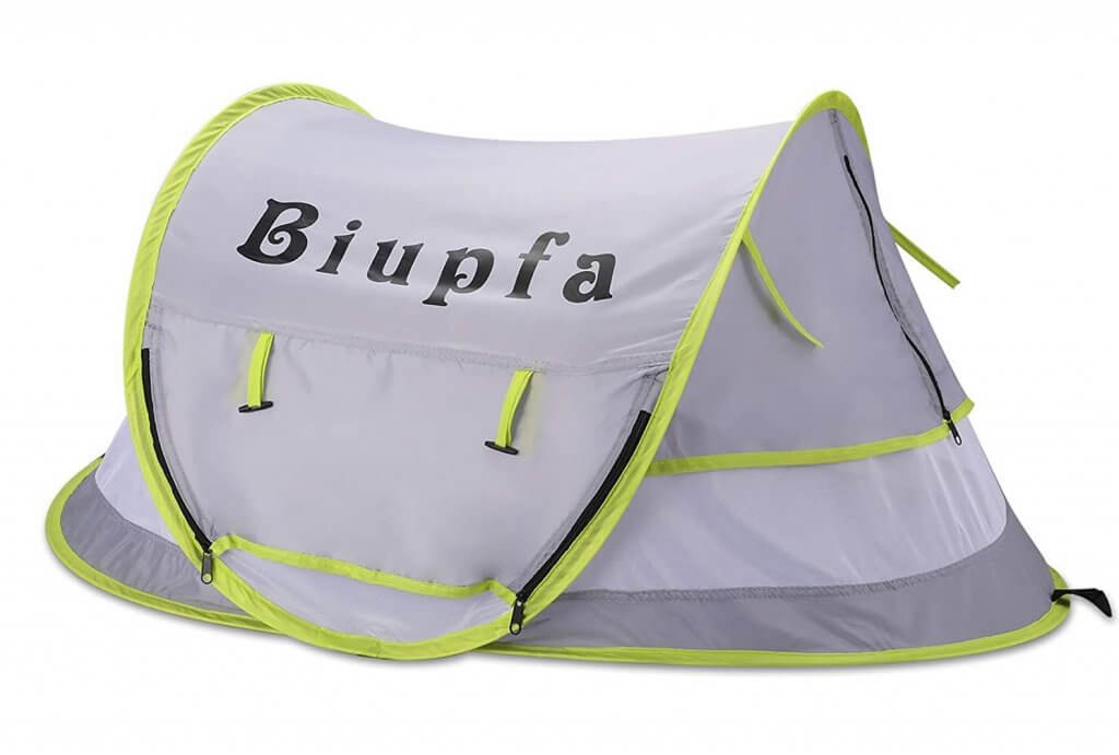 A pop up sun tent is one of the best baby beach necessities. Image of a green and grey baby beach tent.