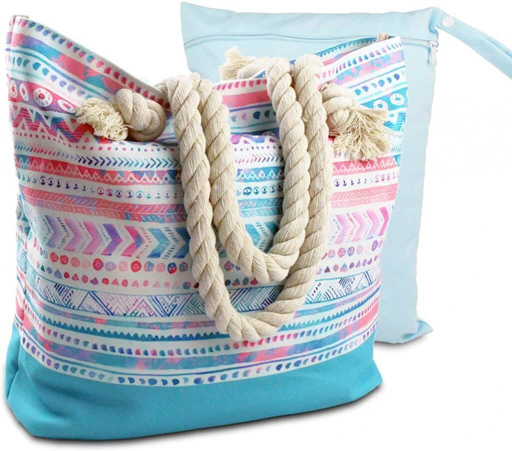 This Boho beach bag is water resistant and comes with a bonus wet/dry bag. Image of a pink and blue beach bag with rope handles.