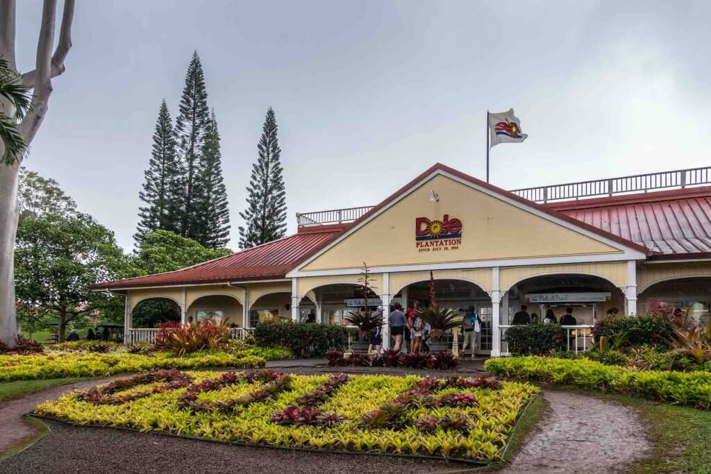Dole Plantation is a top thing to do in North Shore Oahu. Image of the Dole Plantation Welcome Center with shrubs that spell out DOLE and a Dole flag hanging above the building.