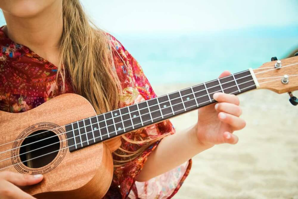 Find out the most famous Hawaiian songs by top Hawaii blog Hawaii Travel with Kids. Image of a child playing the ukulele on the beach.