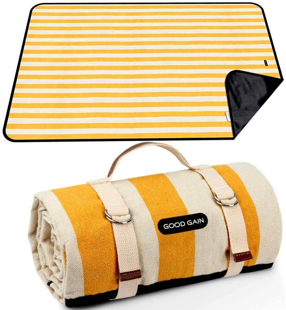 A waterproof and sandproof beach blanket is one of the smartest beach essentials for kids. Image of a white and yellow striped beach blanket.
