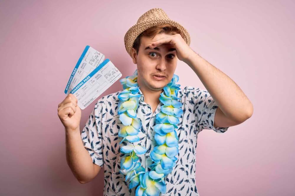Find out the top Hawaii mistakes tourists make from top Hawaii blog Hawaii Travel with Kids. Image of a redhead tourist man on vacation wearing hawaiian lei holding boarding pass and looking stressed out.