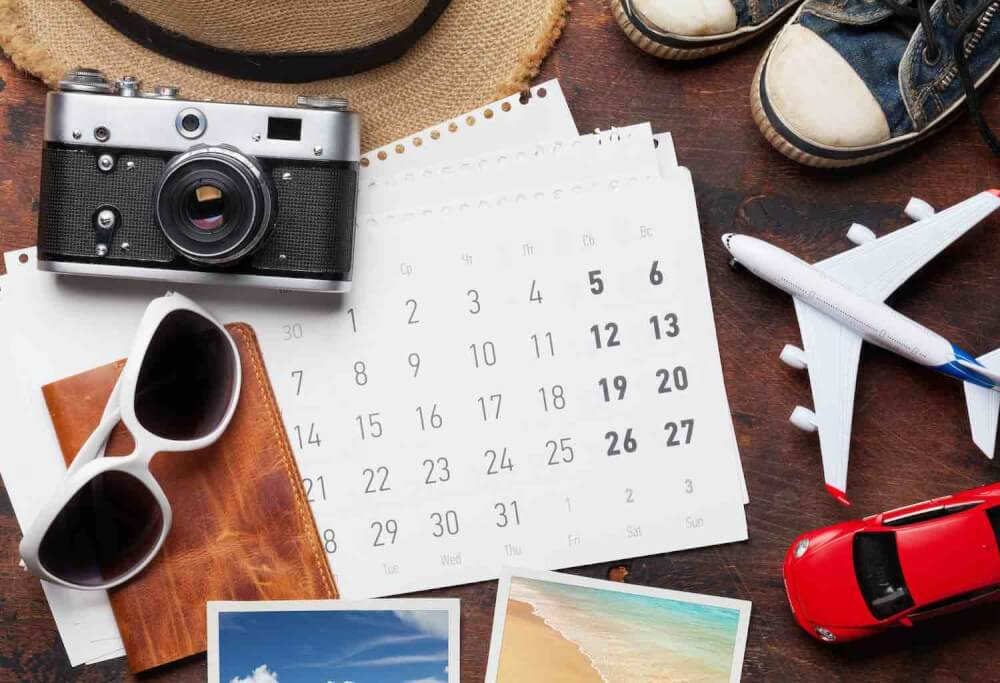 Find out how to plan a trip to Hawaii by top Hawaii blog Hawaii Travel with Kids. Image of travel vacation concept with sun hat, camera, passport, airplane toy and weekend photos on wooden backdrop. Top view. Flat lay.