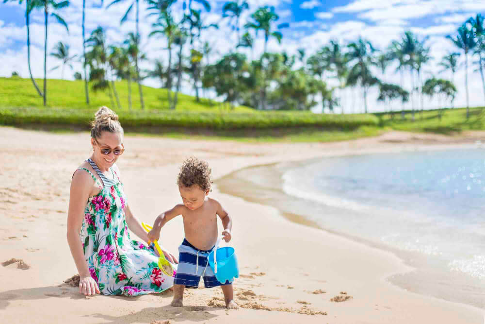 Get this ultimate guide to Hawaii with toddler by top Hawaii blog Hawaii Travel with Kids. Image of a mom and toddler playing in the sand on a beach in Hawaii.