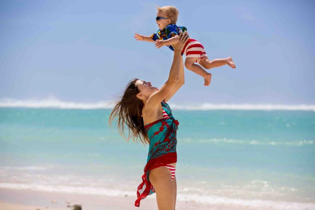 Find out how to travel to Hawaii with a toddler. Image of a mom and child, dressed in Hawaiian shirts, playing together on the beach in Hawaii.
