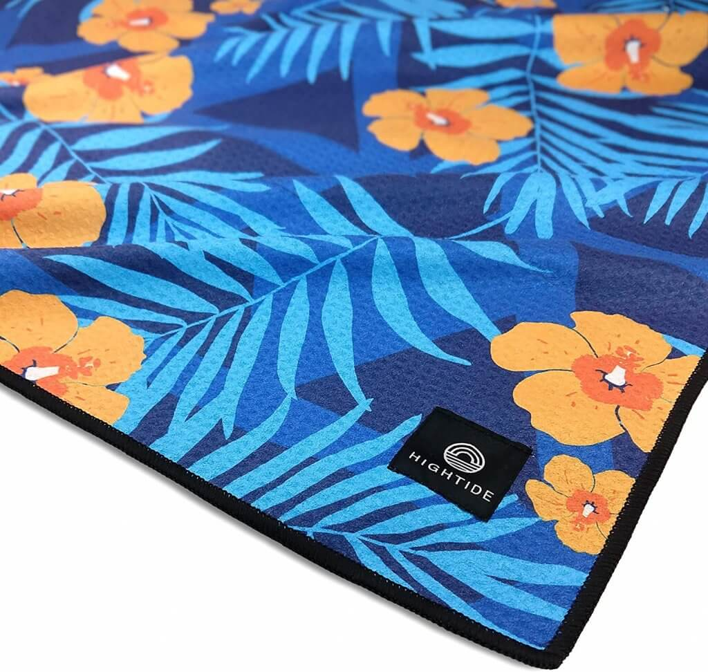 This sandfree beach towel is super handy for traveling to Hawaii with a baby. Image of a orange and blue tropical print towel.