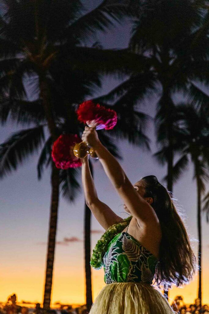 Image of a woman hula dancing with feather gourd rattles at sunset.