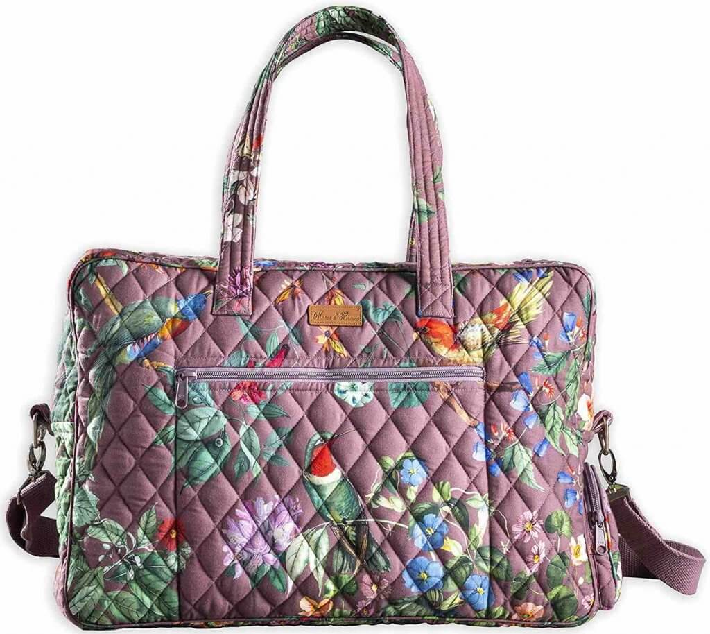 While it's always best to use second hand luggage as your zero waste travel essential, you can always buy one out of recycled or natural materials. Image of a cotton overnight bag that is purple with a tropical print on it.