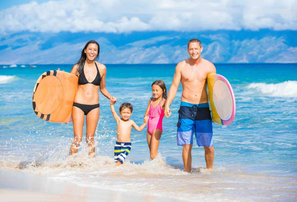 Find out whether Maui vs Oahu is the best Hawaiian island for kids. Image of a family with surfboards on the beach in Hawaii.