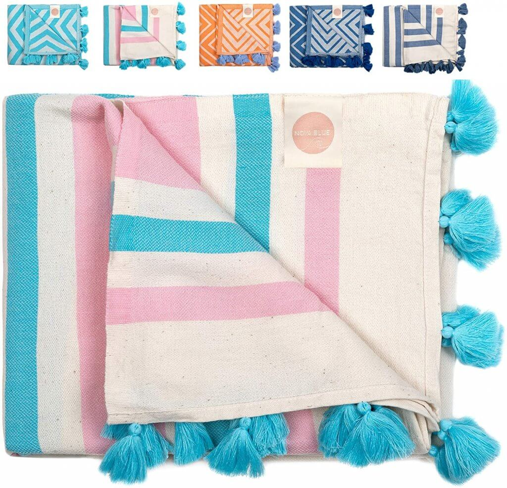 These adorable Turkish towels are some of the best baby gear for the beach. Image of a pink and blue striped Turkish towel with blue tassels on it.