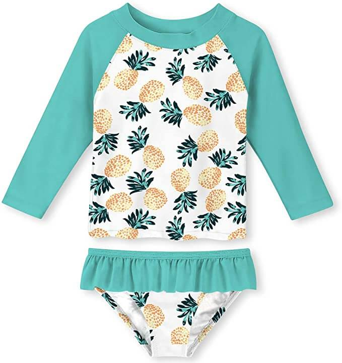 This pineapple print swimsuit is one of the cutest beach baby items. Image of a green and white swimsuit with yellow pineapples on it.