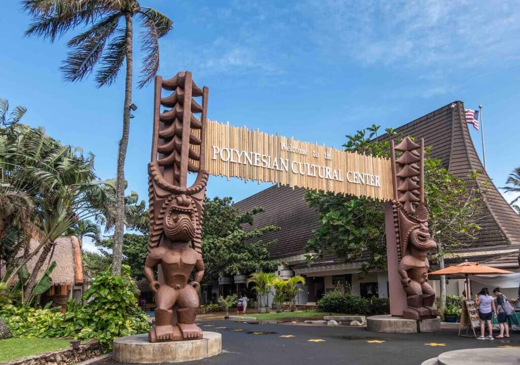 The Polynesian Cultural Center is one of the top Oahu tourist attractions. Image of the Polynesian Cultural Center gate into the park with brown giant tiki statues. People and green vegetation under blue sky.