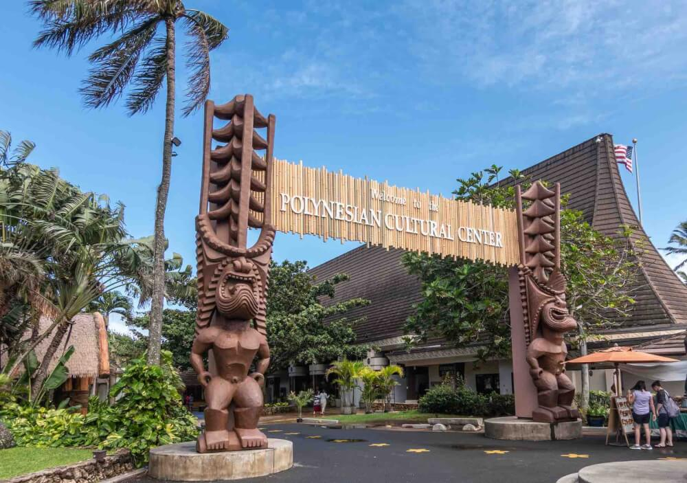 Laie, Oahu, Hawaii, USA. - January 09, 2020: Polynesian Cultural Center. Monumental gate into the park with brown giant aboriginal statues. People and green vegetation under blue sky.