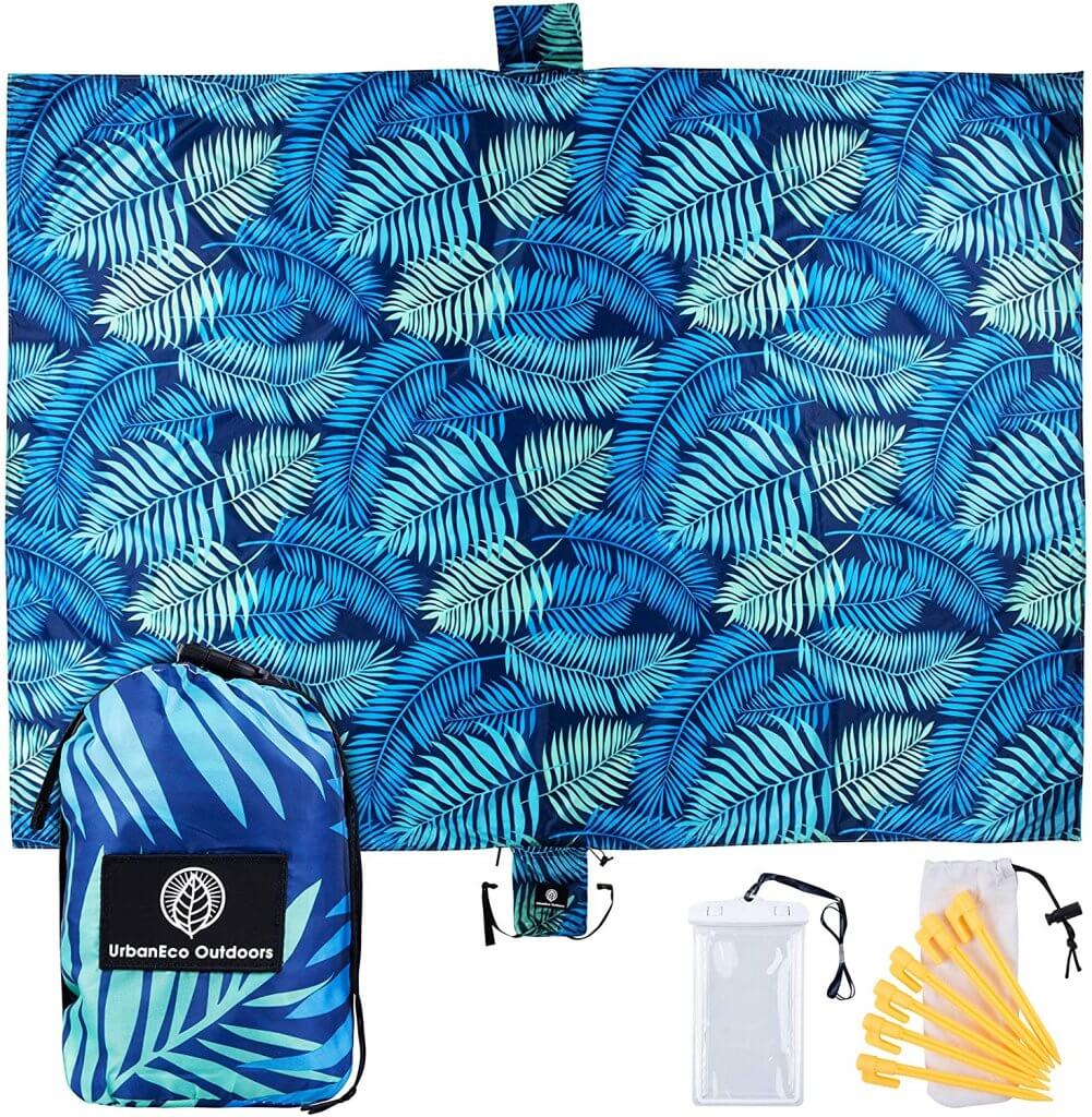A sandfree beach blanket is a top beach must haves for baby. Image of a blue tropical leaf print towel.