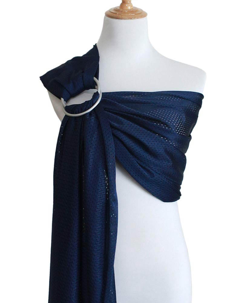A water ring sling is what to take to the beach with a baby if you plan on going into the ocean. Image of a navy blue mesh ring sling for babies.