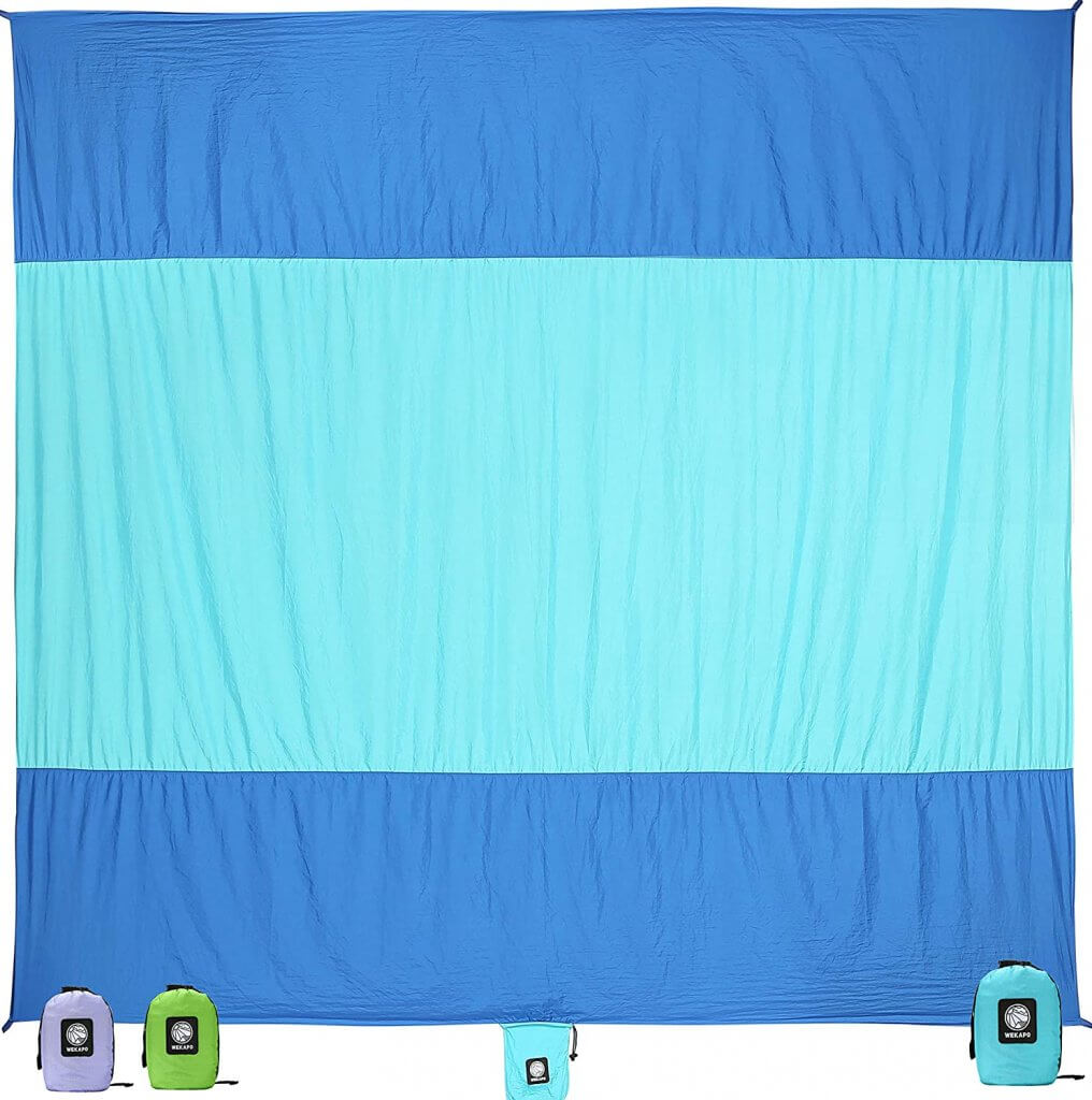 A sand free beach towel is one of the best beach essentials for baby. Image of a blue and teal striped beach towel.
