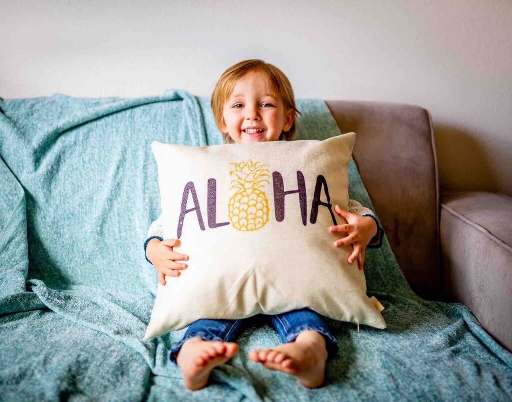 "Find out where to stay in Hawaii with toddlers. Image of a boy holding a pillow with the word ""aloha"" on it."