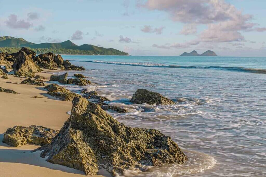 Bellows Beach is one of the best beaches on Oahu for a military vacation to Hawaii. Image of Rock outcropping at the shore of Bellows Beach at dawn on Waimanalo Bay on Oahu, Hawaii.