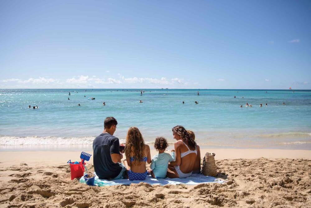 Find out the best Oahu beaches for kids recommended by top Hawaii blog Hawaii Travel with Kids. Image of a family sitting on a beach blanket looking at the ocean.