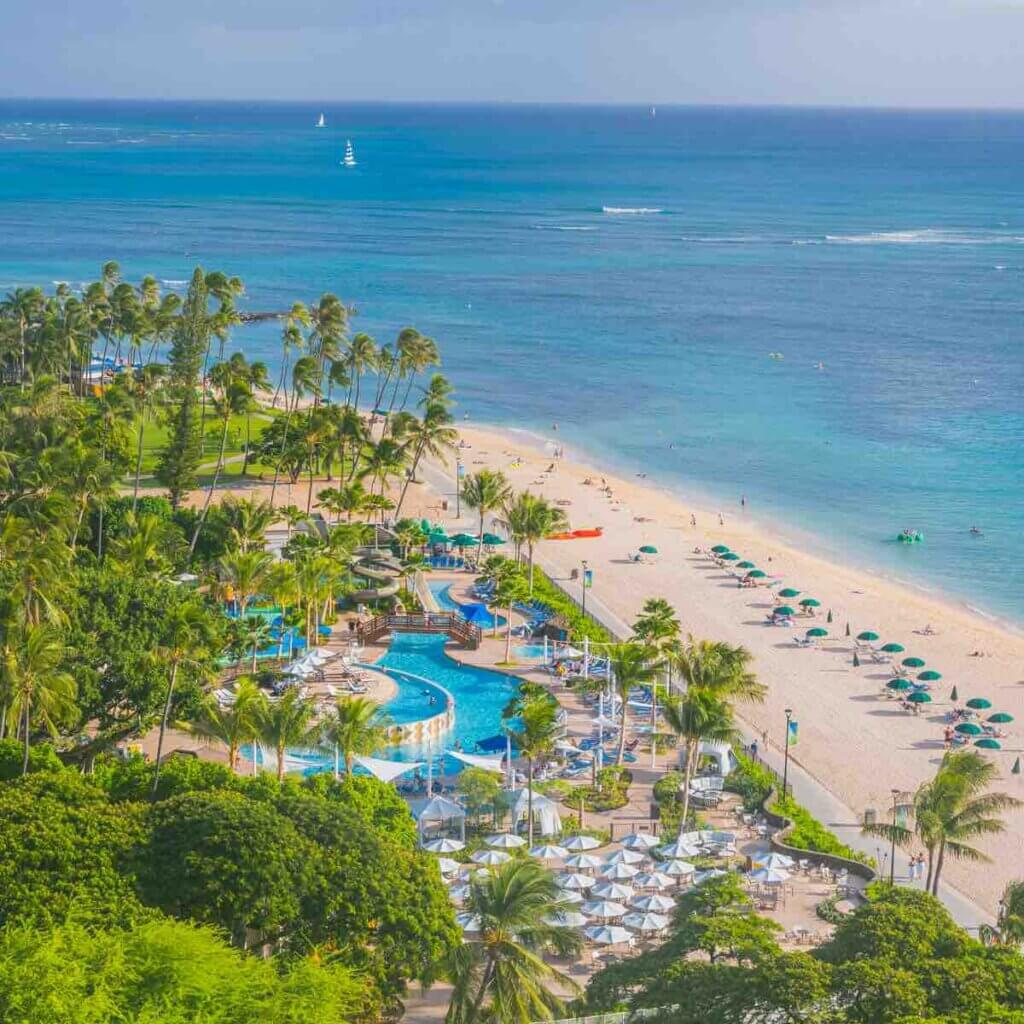 The Hale Koa is the top place to stay for a military vacation to Hawaii. Image of a beachfront hotel with pool area.