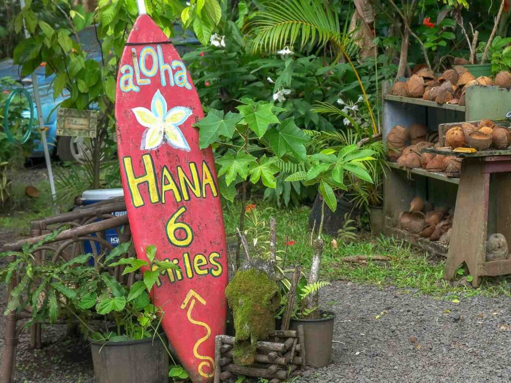 Another fun thing to do in Maui with kids is check out the Road to Hana. Image of a red surfbarod sign that says Hana 6 miles and some fruit in the background.
