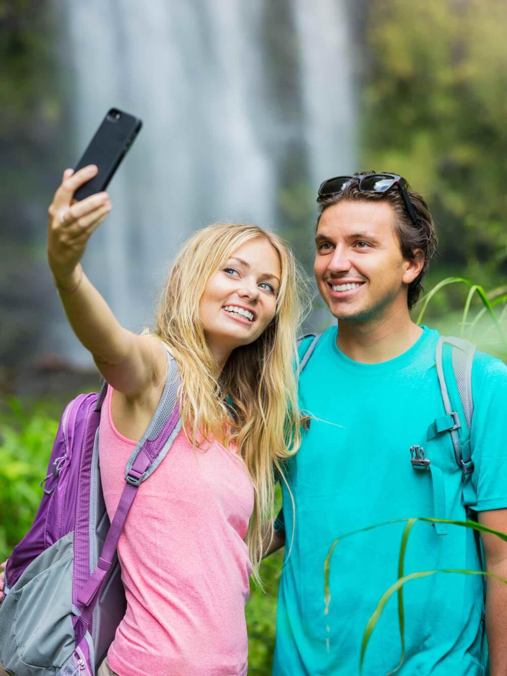 Find out the biggest Hawaii mistakes tourists make in this list by top Hawaii blog Hawaii Travel with Kids. Image of Couple having fun together outdoors. Taking self portrait with camera phone after hiking to incredible waterfall in Hawaii.