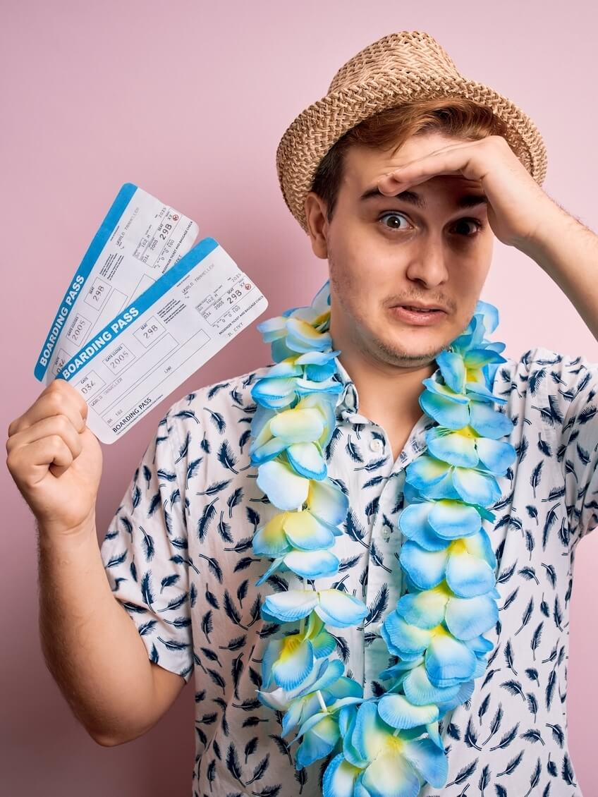 Find out the biggest Hawaii mistakes tourists make by top Hawaii blog Hawaii Travel with Kids. Image of a man wearing a Hawaiian shirt, blue lei, a straw hat, and holding airplane tickets.