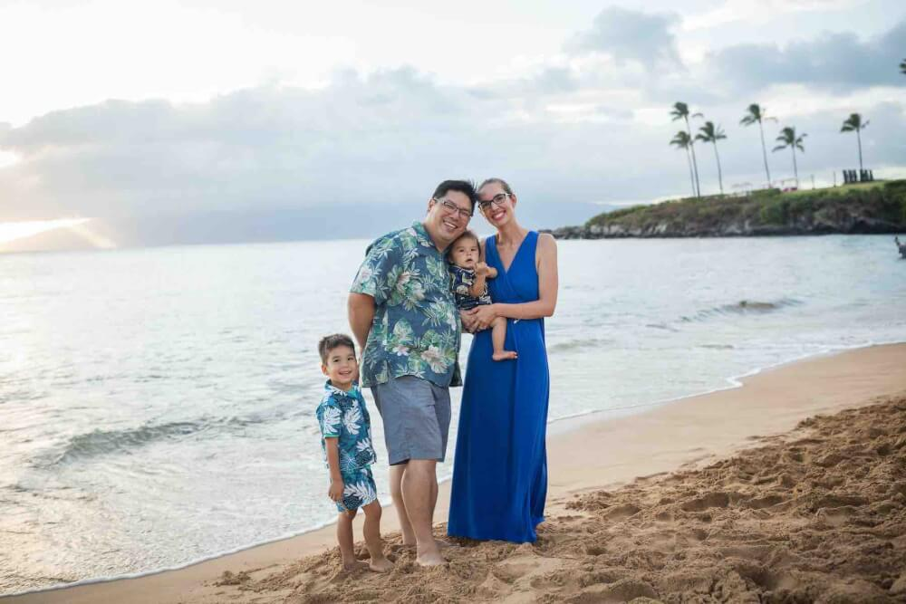 Find out where to book affordable Maui photographers for your Maui family photos by top Hawaii blog Hawaii Travel with Kids. Image of a family wearing tropical clothing posing on a beach in Maui.