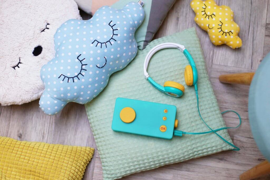 Lunii is the best airplane toy for toddlers. Image of a blue and yellow rectangular box and headphones on a bunch of pillows.