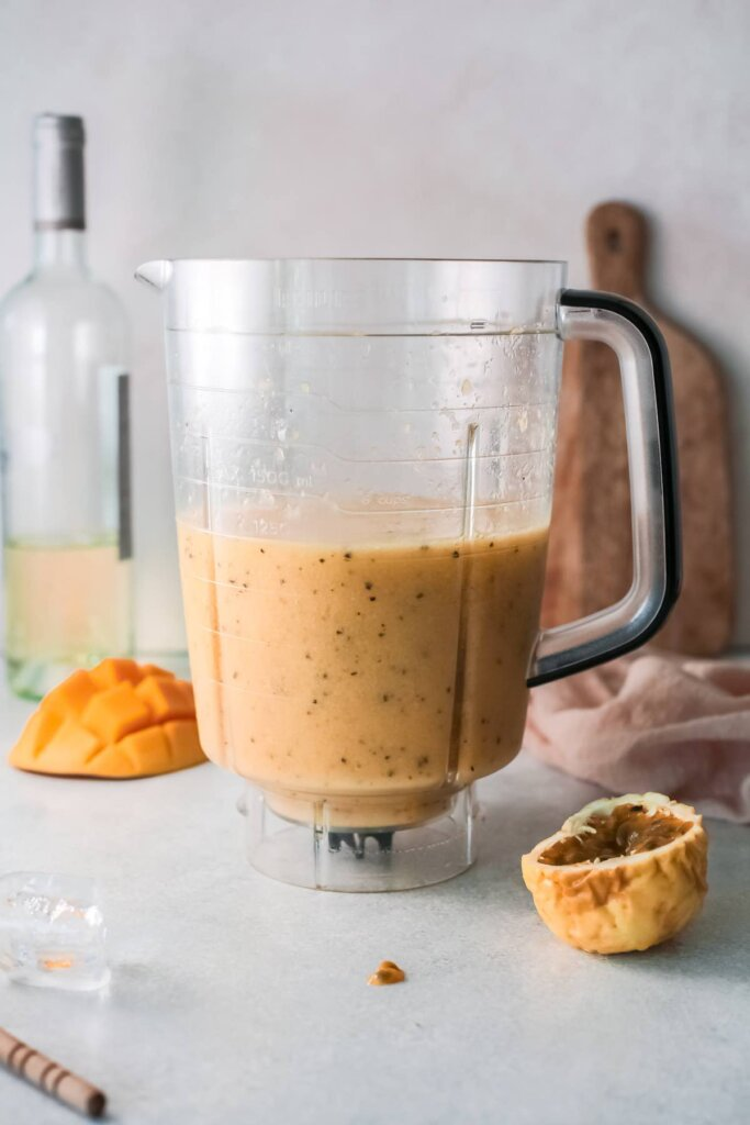Add the ice to the mango passion fruit mix and blend together. Image of a blender filled with a Mango Passion Fruit Wine Slushie