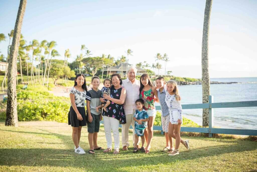 We love booking afforable Maui photographers when we do multigenerational travel. Image of grandparents with 7 grandkids in Hawaii.