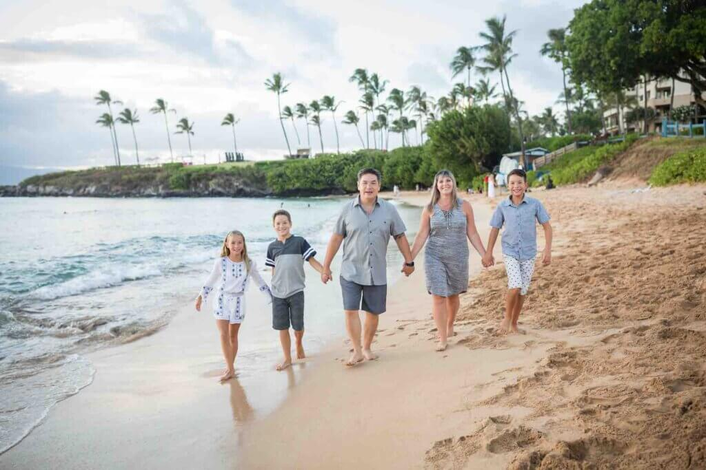 Get the cutest Maui family photos at the beach during golden hour. Image of a family of five holding hands and walking on the beach.